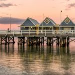 The iconic blue Busselton Jetty buildings at sunset
